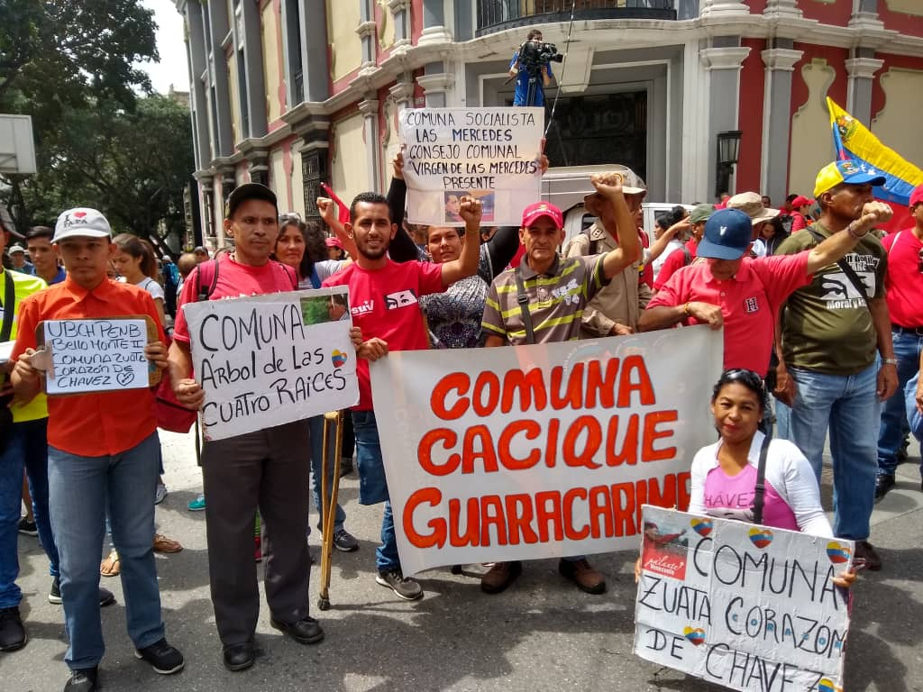 Representatives from the Tree of Four Roots Commune, Guaracarine Cacique Commune, Zuata Heart of Chavez Commune and Las Mercedes Socialist Commune show their banners at the march. (@Infocomunal / Twitter)
