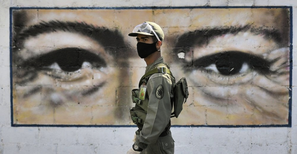 Venezuelan soldier in front of a mural featuring Hugo Chávez's eyes. (AP)