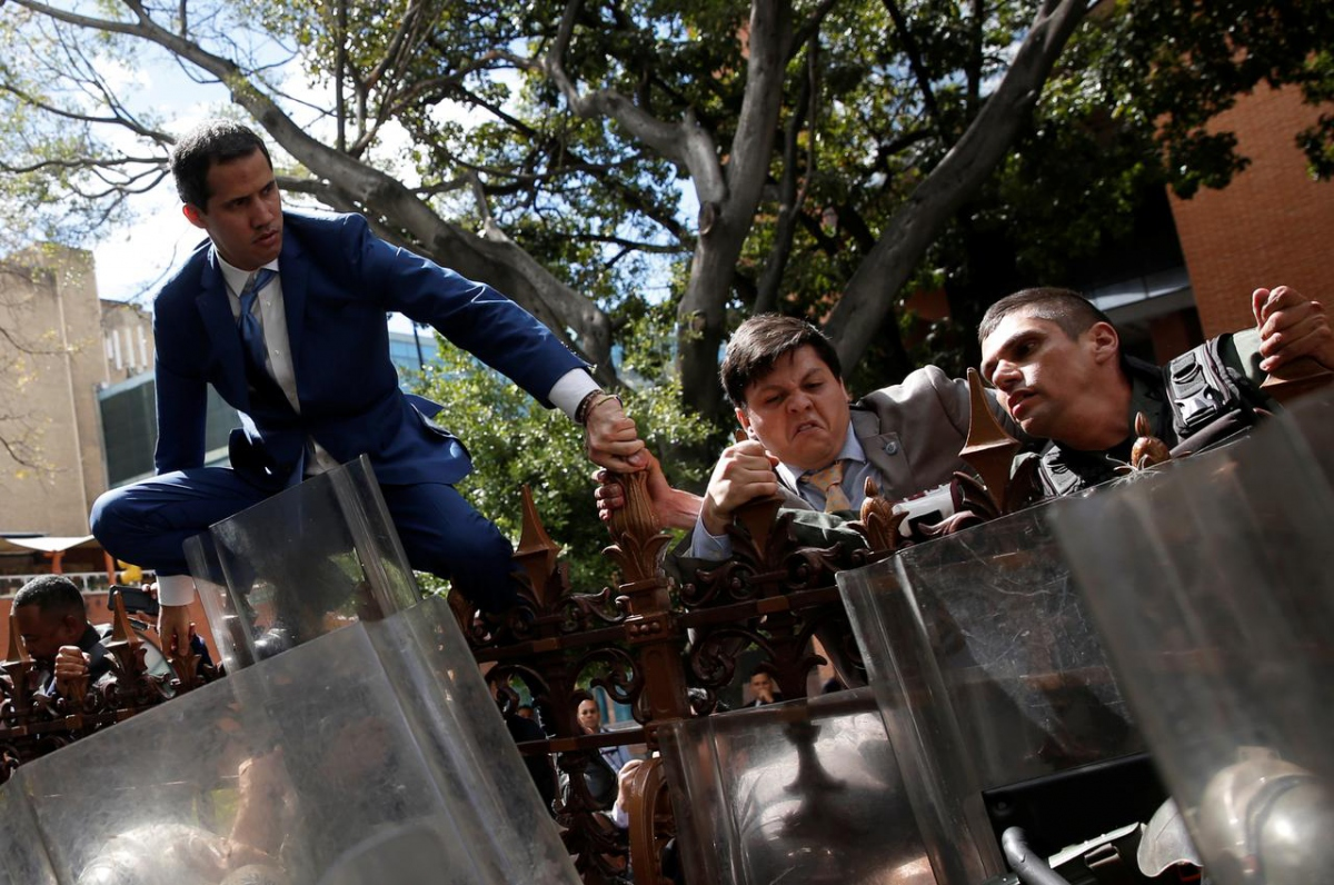 Guaido attempted to scale a fence before the vote took place. His claims that he was barred from entering have been disputed. (Reuters)