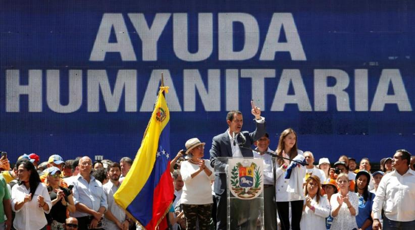 "Juan Guaido addresses followers in Caracas in front of a sign saying ""Humanitarian Aid"" (ABC)"