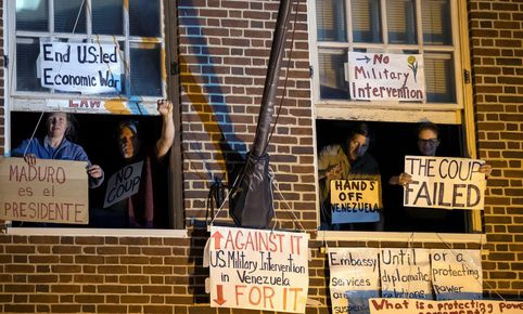The four members of the Embassy Protection Collective hang signs from the windows of the diplomatic building before being evicted. (EFE)