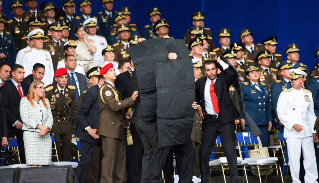 Bodyguards cover the president as drones carrying explosives are shot down close to his platform (@XHNews / Twitter)