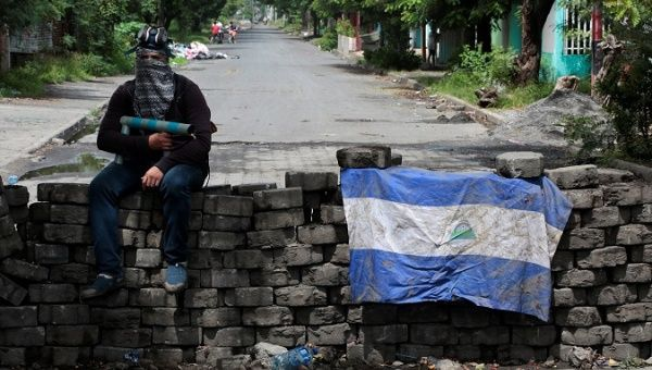 A man holding a homemade mortar sits on a roadblock in Managua, Nicaragua June 16, 2018. (Reuters)