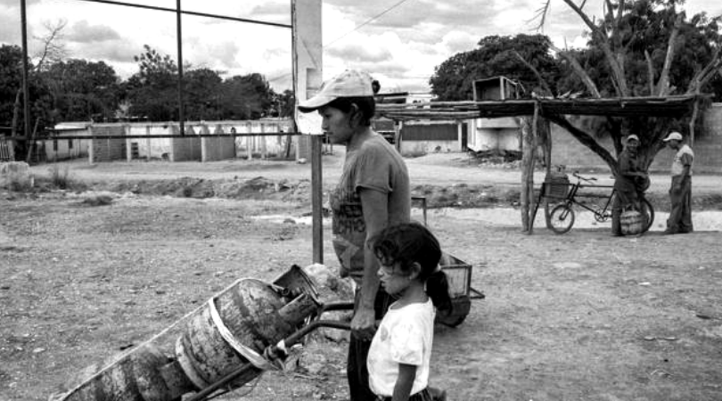 A Venezuelan mother and her daughter carry a gas cylinder. (Archive)