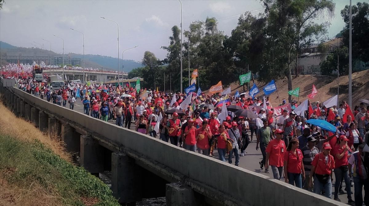 Workers march past La Bandera in Caracas. (Katrina Kozarek)