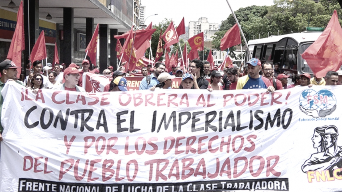 "The banner reads ""Working Class to Power! Against imperialism and for all the rights of the working people."" (Tribuna Popular)"