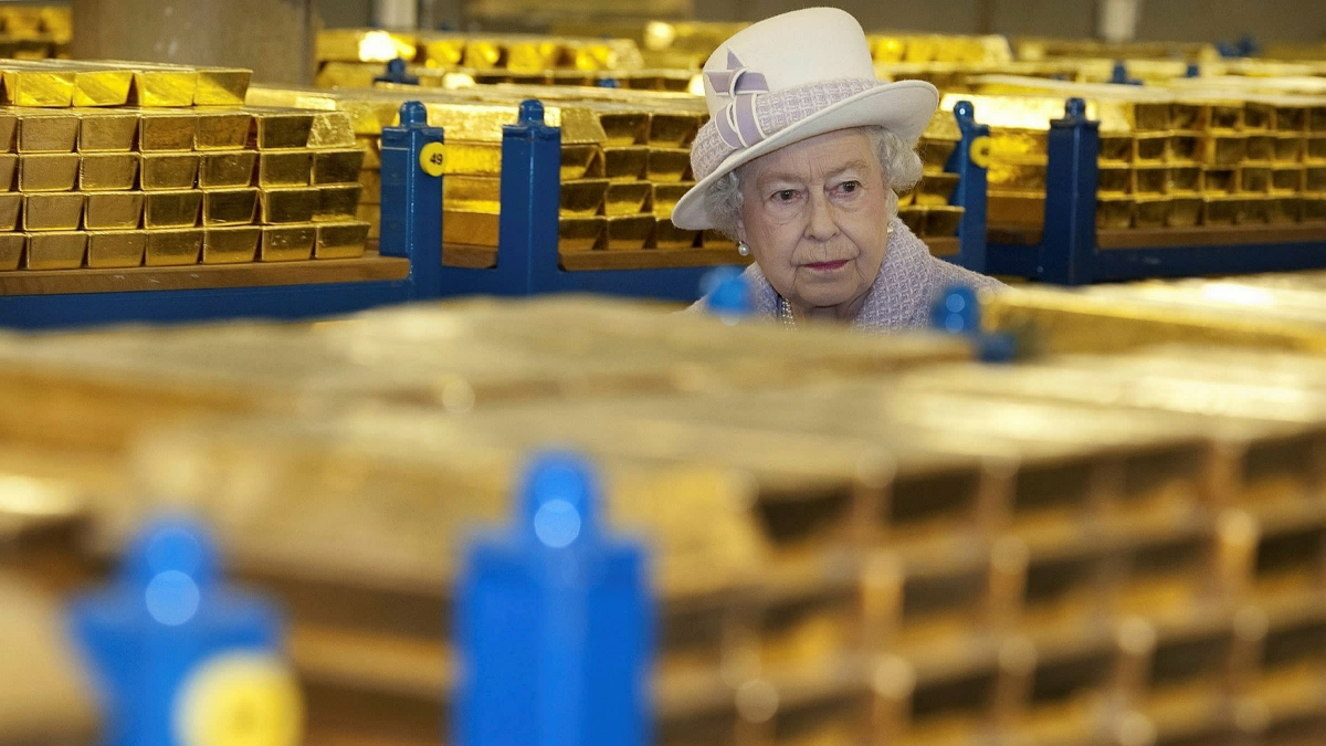 Queen Elizabeth II examines stacks of gold bullions. (Reuters)