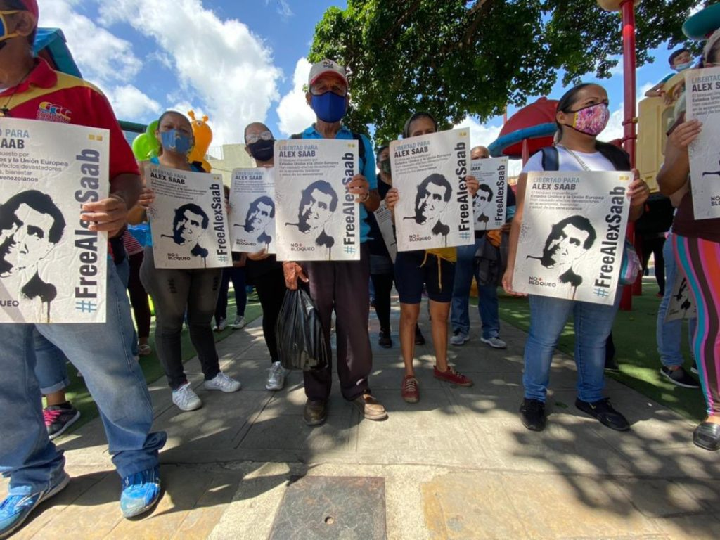 Demonstrators hold up signs calling for the release of Alex Saab. (@SPerezPSUV / Twitter)