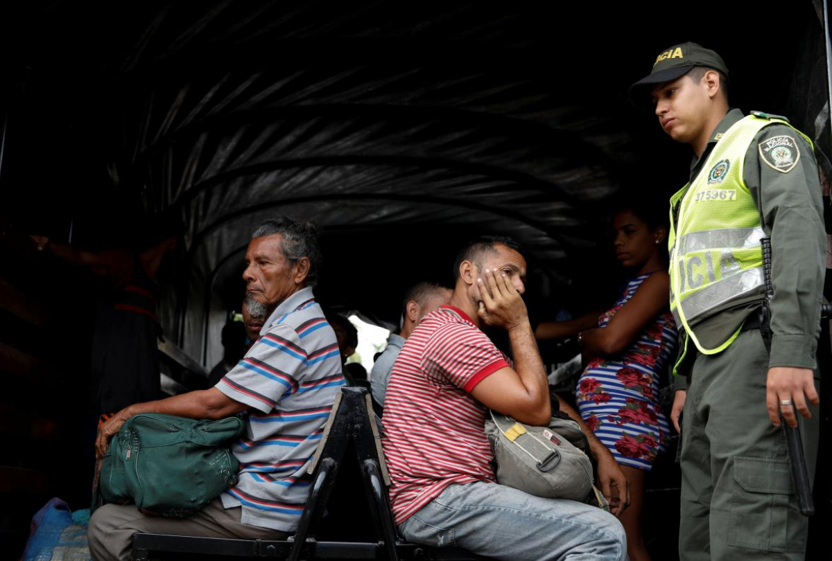 Venezuelans evicted from the camp wait on a Colombian police truck to be escorted back to Venezuela. (Reuters)