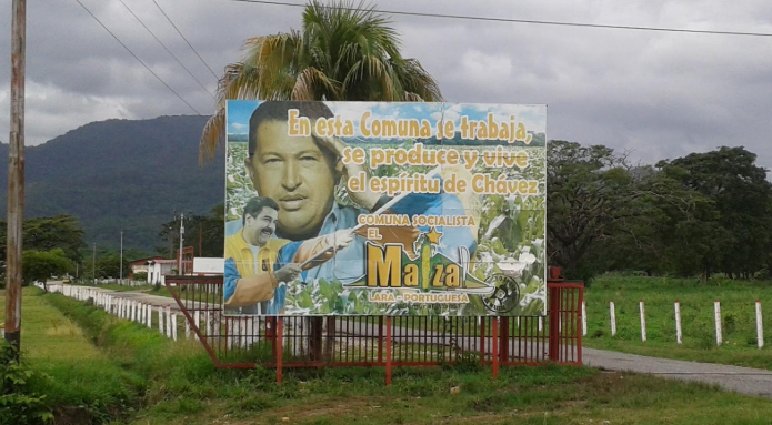 """In this commune we work, produce and live the spirit of Chávez."" Billboard at the entrance of the El Maizal commune. (Ricardo Vaz)"