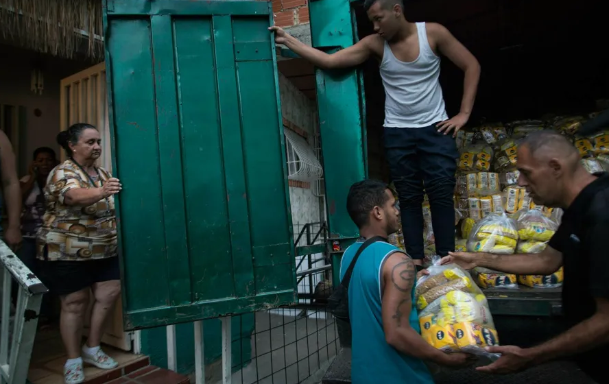 "Neighbors download subsidized food distributed under a government program named ""CLAP,"" in the Catia district of Caracas, Venezuela, on Thursday, January 31, 2019. (AP / Rodrigo Abd)"