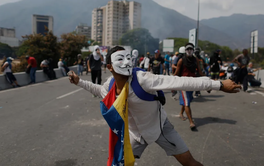 An anti-government protester throws a rock toward security forces inside La Carlota airbase in Caracas on May 1, 2019. (AP/Ariana Cubillos)
