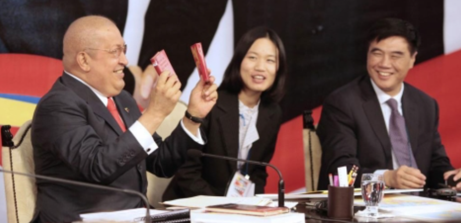 "Hugo Chávez displays two copies of Mao's ""Little Red Book,"" 2011. (MinCI)"