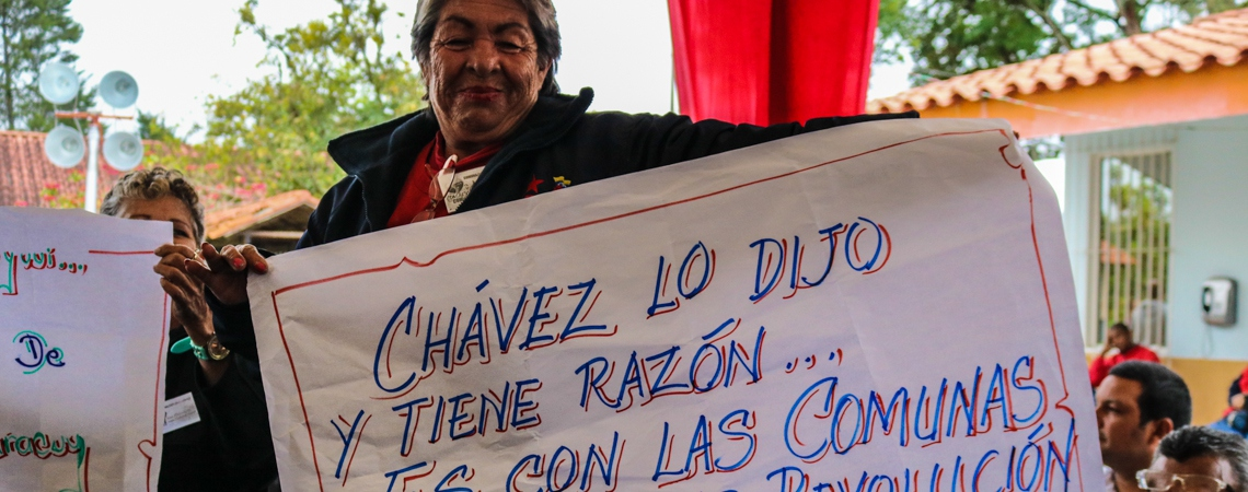 "A woman holds a banner that reads, ""Chavez said so, and he was right… it is with the communes that we will do the revolution."" (Archive)"