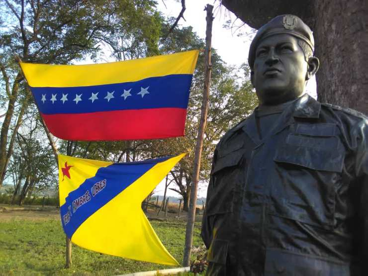 "In El Maizal Commune, under an enormous saman tree, visitors will find a sculpture of Hugo Chavez. Behind it, the Venezuelan flag and the Zamora flag, which reads ""Free land and free men."" (Cira Pascual Marquina/Venezuelanalysis)"