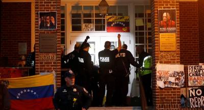 US police begin the nighttime raid to evict the Embassy Protection Collective in violation of the Vienna Convention and international law. (Sputnik)