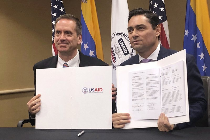 USAID director Mark Green and Guaido representative Carlos Vecchio signed the agreement on Tuesday. (AP)