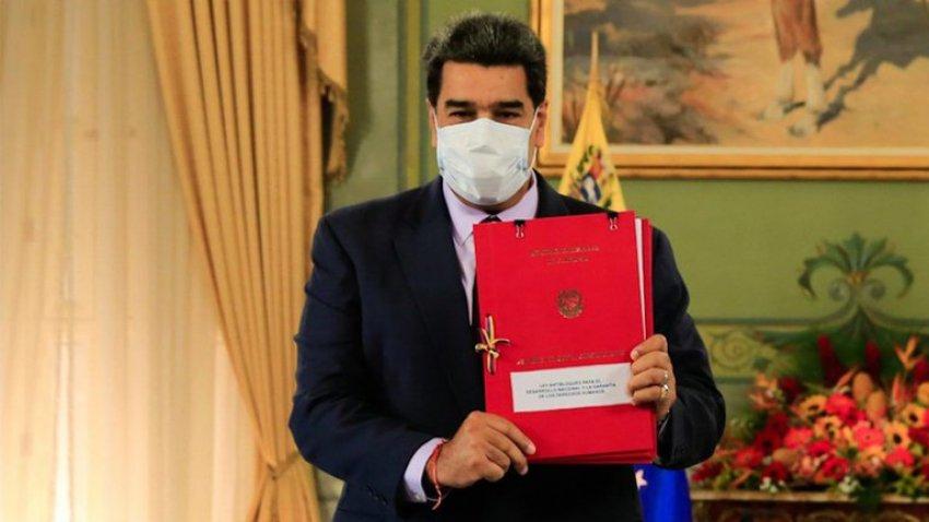 Venezuelan President Nicolas Maduro holds up a copy of his anti-blockade law (MPPCI)