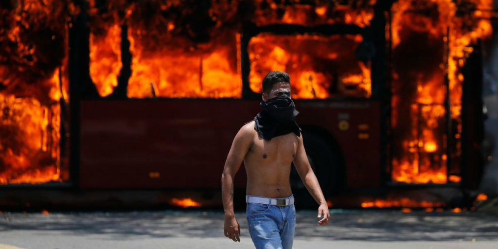 Coup supporter in front of a burning bus. (Fernando Llano/AP)