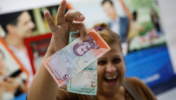 Venezuelan woman showinh the new soveriegn Bolivars. (Reuters)