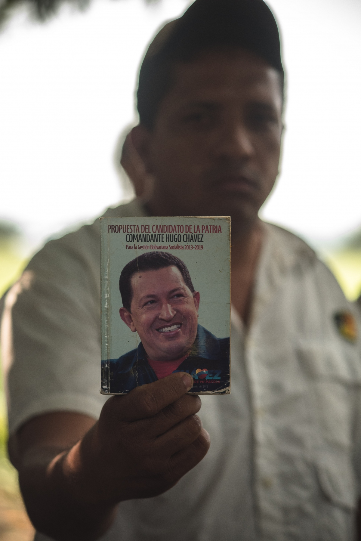 A local resident holds up a book containing proposals by Hugo Chavez. (Marcelo Volpe)
