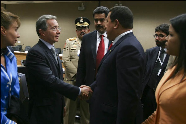 Venezuela's President Chavez and Colombia's President Uribe shake hands at the UNASR summit, while Chavez's daughter (far right) looks on. (Francisco Batista/Prensa Presidencial)