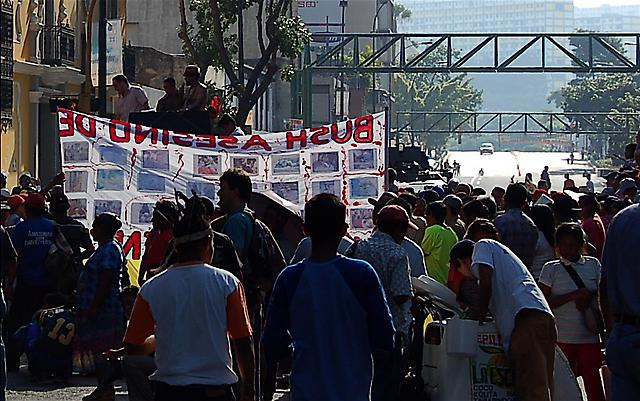 The march pauses in front of the Vice-president's office, while Police block Llaguno Bridge in the background. (Credit: Michael Fox)