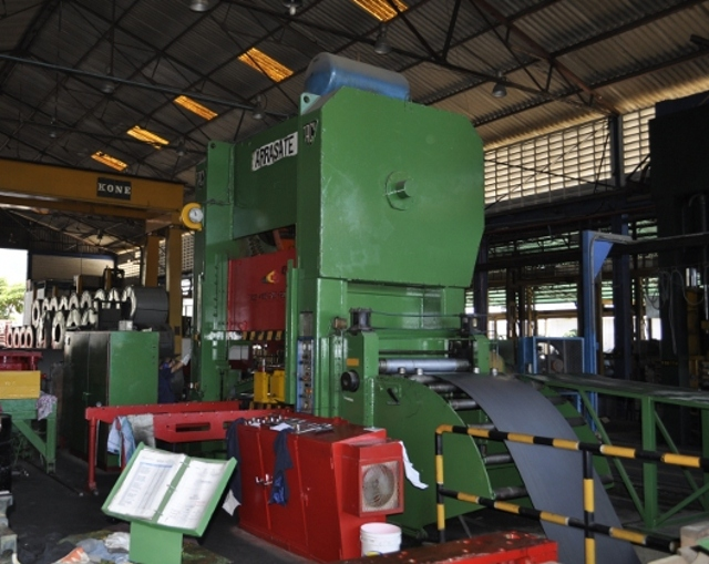 Specialized machinery is used to cut sheets of metal for different sized at-home gas tanks (YVKE Radio Mundial).
