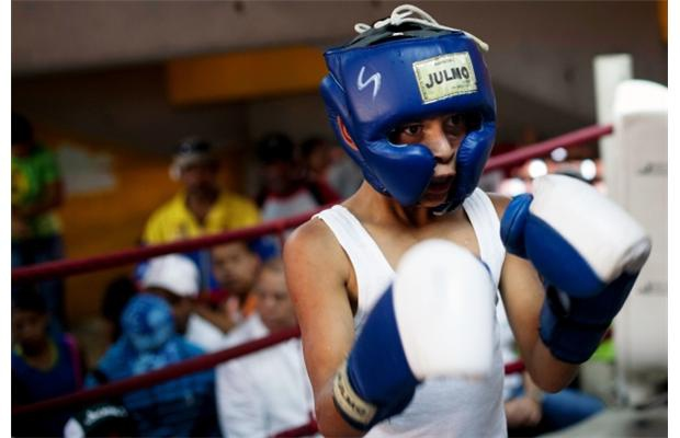 Luis Villanueva, 11, gets ready during his fight in an Olympics-style street boxing championship in Caracas March 5, 2011. (Carlos Garcia Rawlins - REUTERS)
