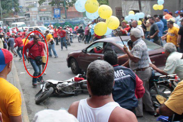 "A man with a gun and in red t-shirt in Cotiza on Sunday. According to members of the community and the government the man was ""infiltrating"", pretending to be with the PSUV (anonymous)."