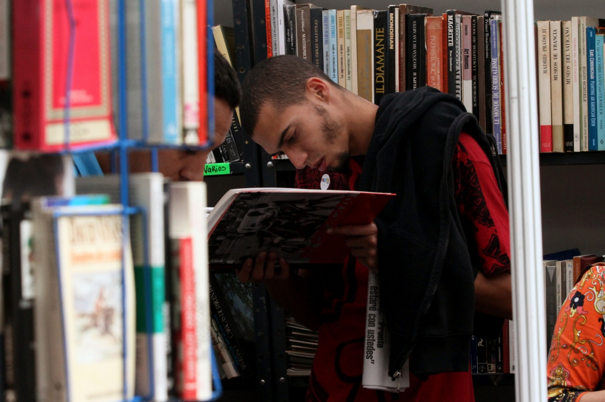 A young man concentrates intently in one of the book stalls (AVN)