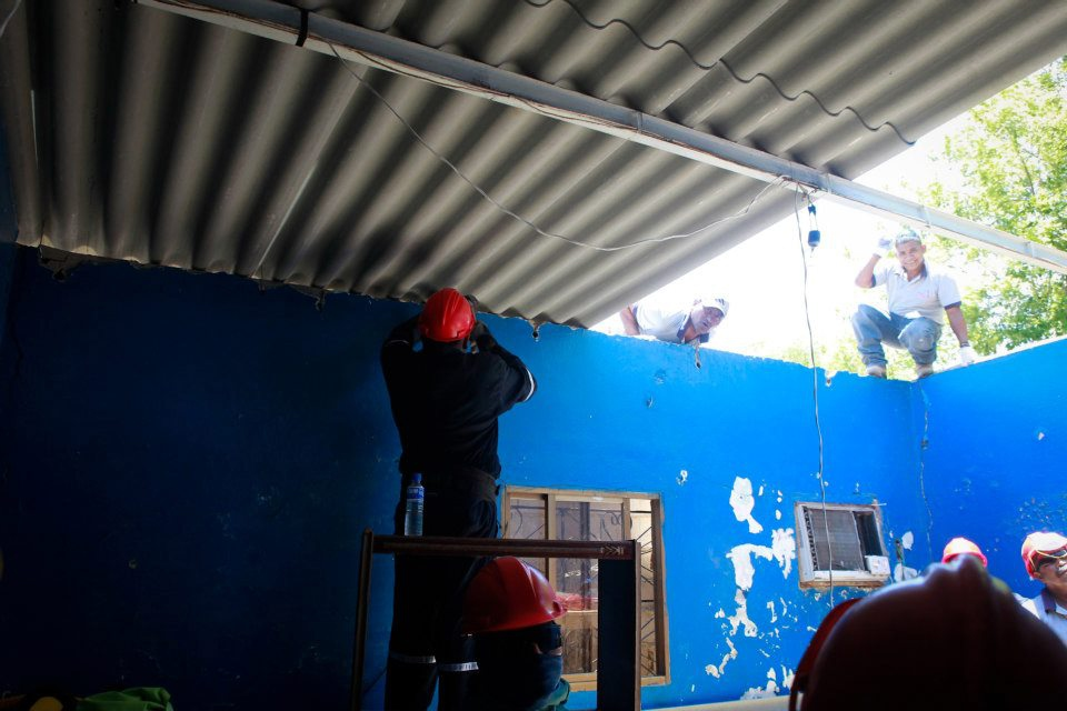 Volunteers and PDVSA workers help repair a damaged roof near the Amuay refinery (YVKE Mundial)