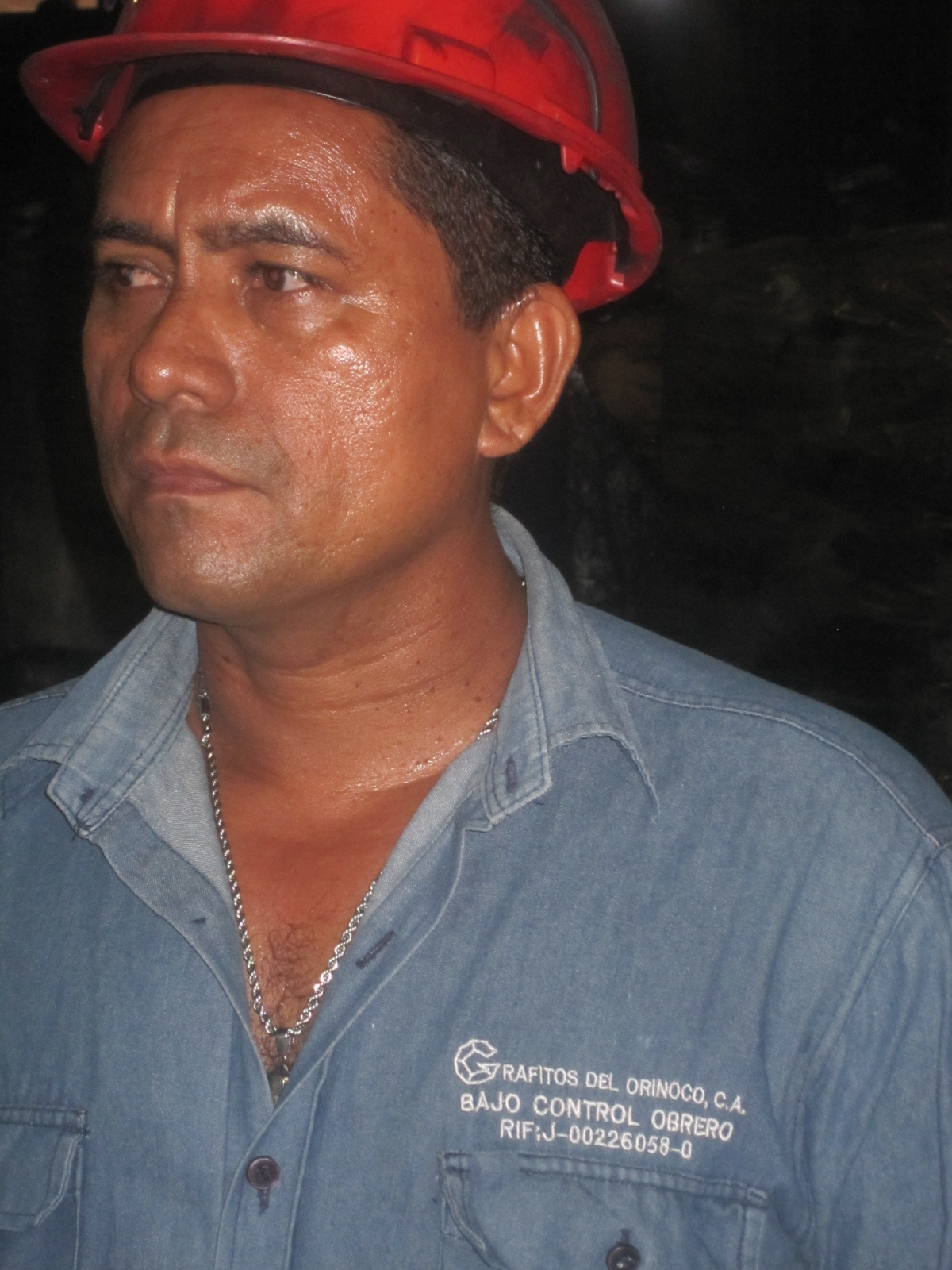 "A Grafitos worker, April 2011. His overall reads, ""Grafitos del Orinoco: Under Worker Control"". (Ewan Robertson)"