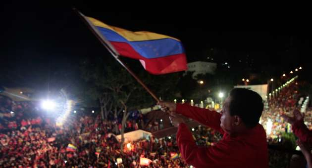 Hugo Chavez waving the Venezuelan flag to supporters from the People's Balcony of the presidential palace, Miraflores, on Sunday night, after his victory was announced (AVN).