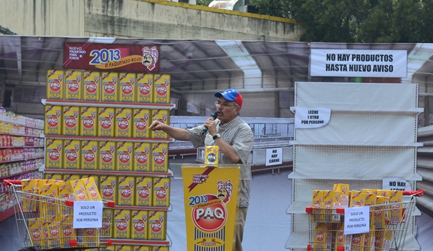 Opposition legislator Ismael Garcia speaks to the crowd in front of a backdrop of empty supermarket shelves (Gregory Quiñonez / Noticias24)