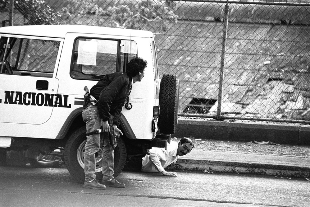 A man seeking cover behind a jeep of newspaper El Nacional (National Library / El Nacional)