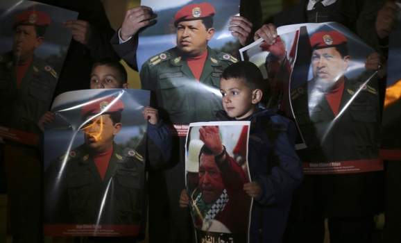 Palestinians hold posters depicting Venezuela's late president Hugo Chavez during a vigil outside the Venezuelan consulate in the West Bank city of Ramallah, March 6, 2013. (Reuters /Mohamad Torokman)