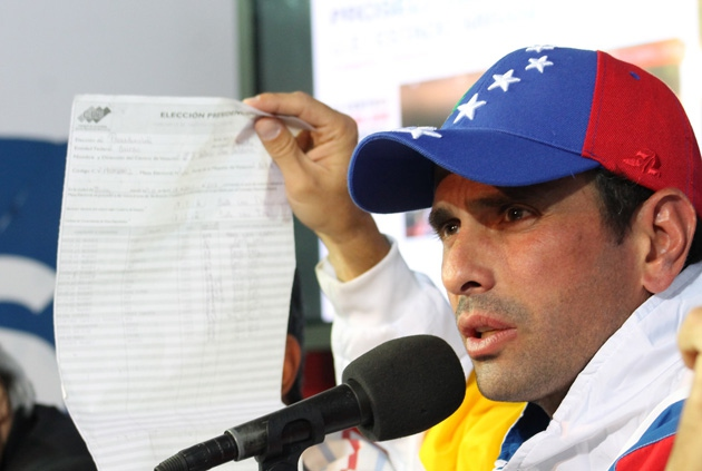 Henrique Capriles holds up an electronic vote tally at yesterday's press conference (Lenin Morales – Cristina Moure / Prensa Comando Simón Bolívar)