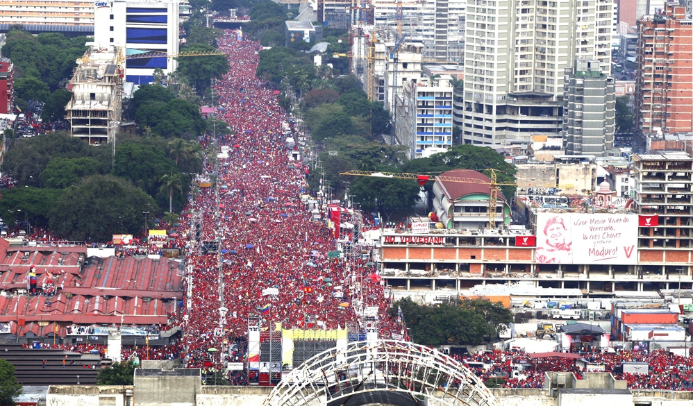 """Billboards in tribute to Chavez and declaring """"they won't return"""" (in reference to Venezuela's old ruling class) surround a packed Avenida Bolivar (Alex Guzman / AVN)"""