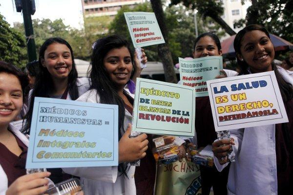 "A group of trainee community doctors on a celebratory march in Caracas. Their placards read ""healthcare is a right, let's defend it"", ""the revolution's army of white jackets,"" and ""community doctors = humane doctors"". (CdO)"