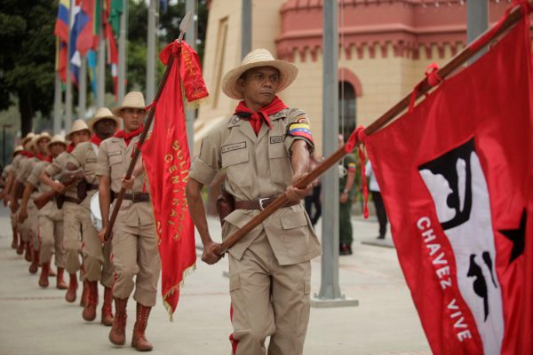 """Ceremonial soldiers at the event. The lead flag reads """"Chavez lives"""". (Sibci)"""