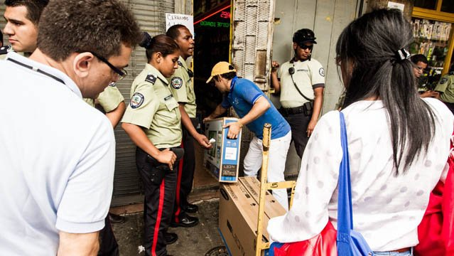 Buying electric goods under police supervision from an occupied store (EFE)