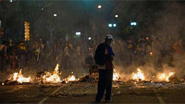 Nightly riots and street barricades continue in upmarket areas of eastern Caracas (AFP)