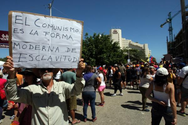 "One of the protestors outside the state run Hotel Venetur, where the Cuban team was staying. His placard says ""communism is the modern form of slavery"" (YVKE Mundial)."