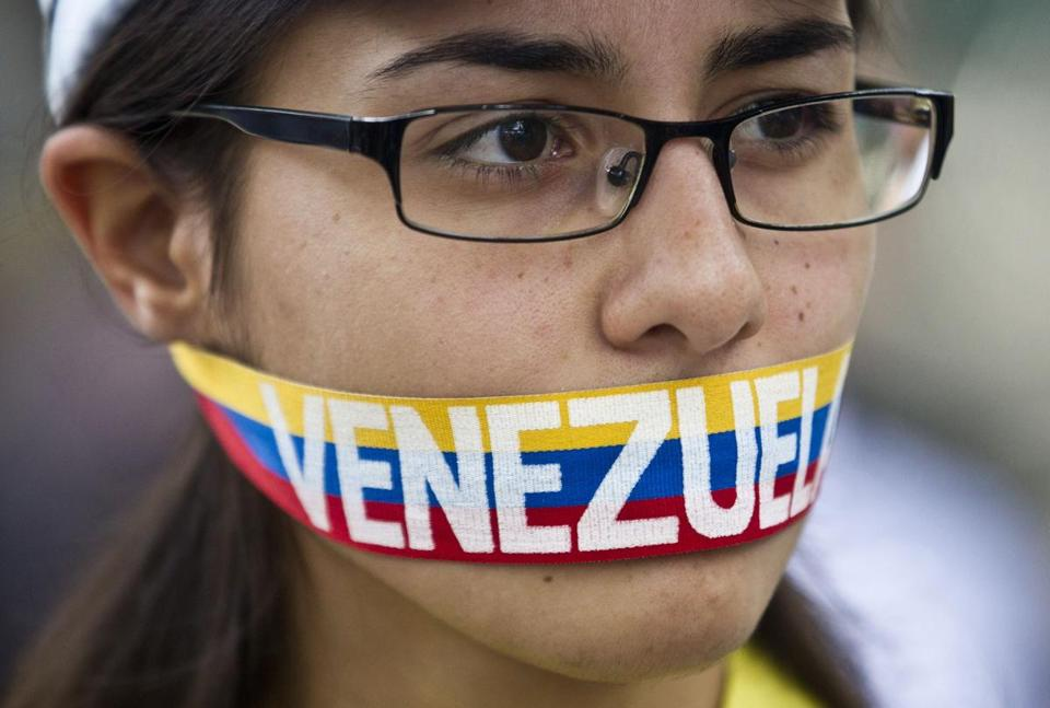 An antigovernment demonstrator stood with a ribbon covering her mouth during a protest in front of an office of the Organization of American States in Caracas. (AP)