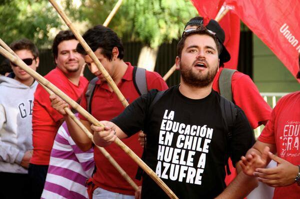 """Chilean student awaits Maduro's arrival outside Venezuelan Embassy in Santiago. His shirt reads """"The education in Chile smells like sulfur."""" (TeleSUR)"""