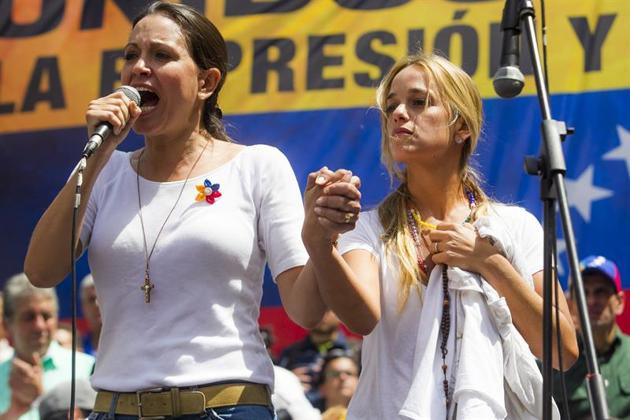 Maria Corina Machado (left) stands with Lilian Tintori, wife of imprisoned opposition leader Leopoldo Lopez while addressing a protest in Caracas on Saturday, February 22nd. (EFE/Miguel Gutiérrez)