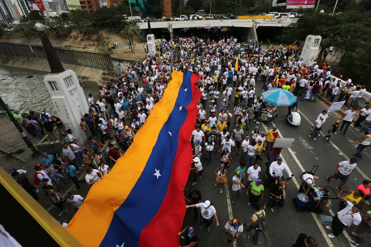 Demonstrators display a Venezuelan flag during a protest in Caracas, Venezuela, Sunday, March 2, 2014. (AP Photo/Fernando Llano)