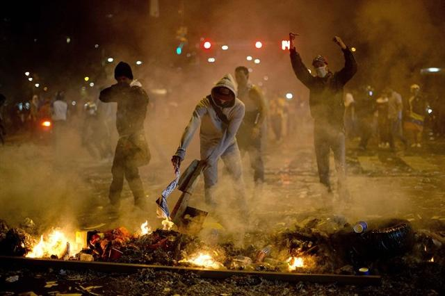 Anti-government demonstrators burn trash at a barricade in wealthy neighborhood of Alta Mira, Caracas, in February (AP /Rodrigo Abd)