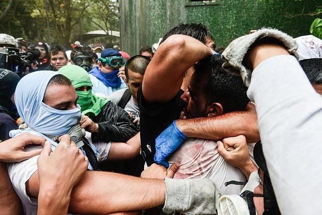 Caption: Unidentified emergency medical technician attempts to protect Muñoz. (Carlos Becerra/Demotrix)
